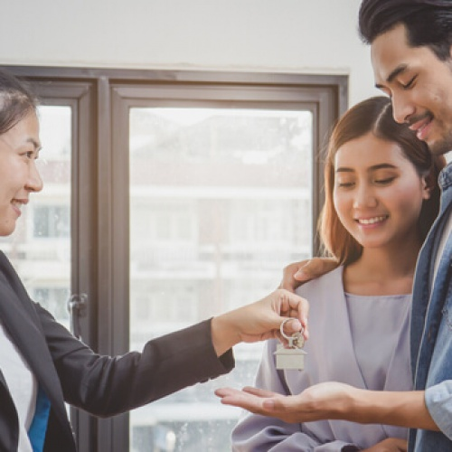 Landlord giving keys to couple