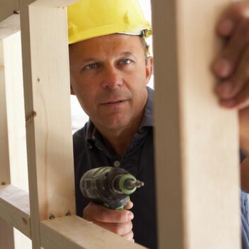 A builder hammering a frame
