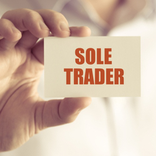 Man holding a card saying Sole Trader