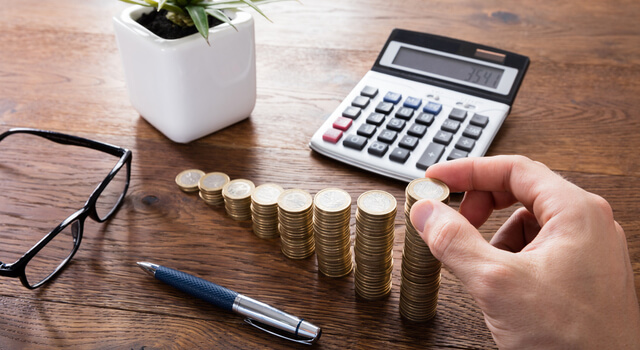 A stack of coins and calculator